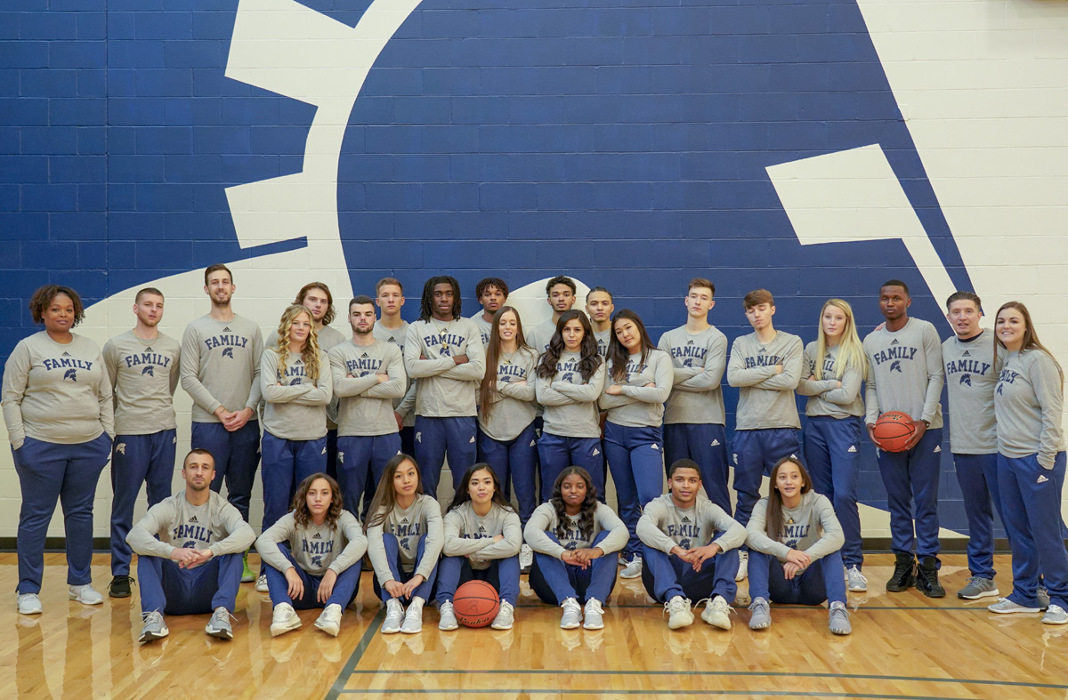 Men's and Women's 2019 Basketball teams posing in front of the titan helmet in the gym, wearing Titan Family shirts.