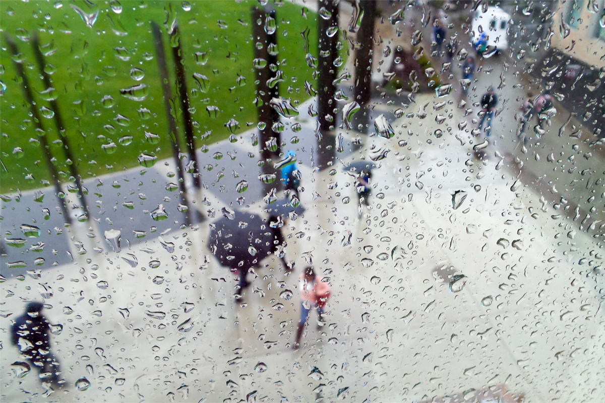 Aerial view through a rainwashed window of students walking across the Trustee Plaza, some with umbrellas