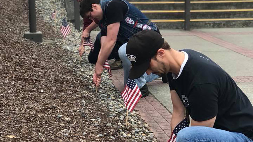 students placing ameriencan flags for veterans