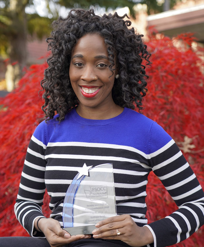 Latoya reid with an award in front of a tree near building F1