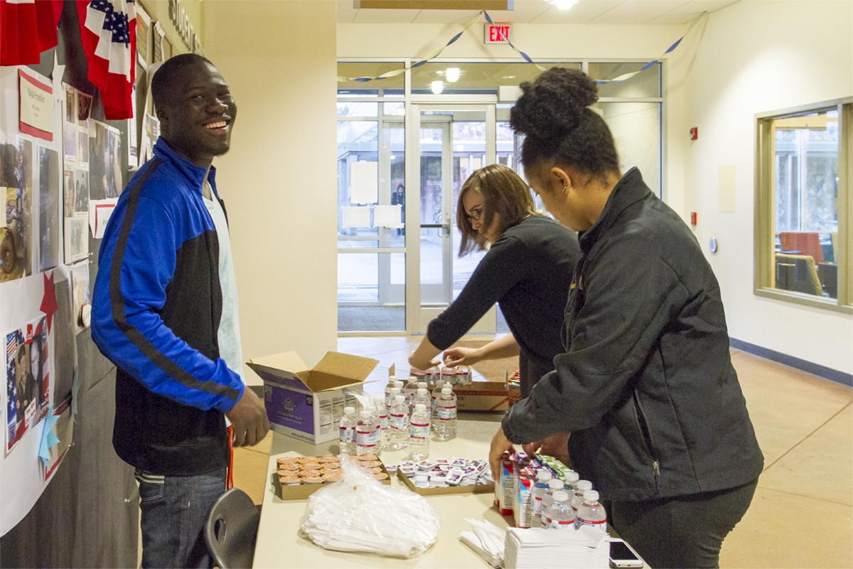 A smiling male student and two female students distribute snacks in the Student Center