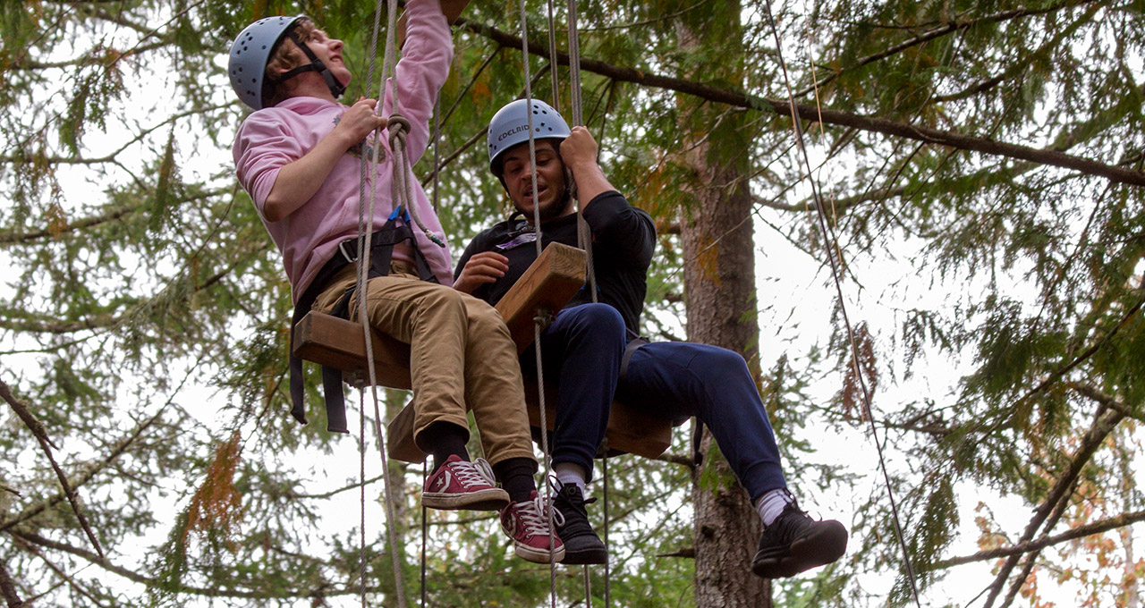 Two TCC Men of Distinction students hanging from ropes in a forest