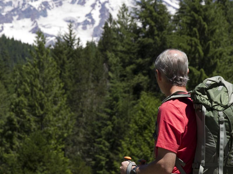 A man with a backpack standing on a trail looking towards Mount Rainier