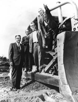 Group of men standing on construction equipment at TCC campus in 1965. Black and white photo.